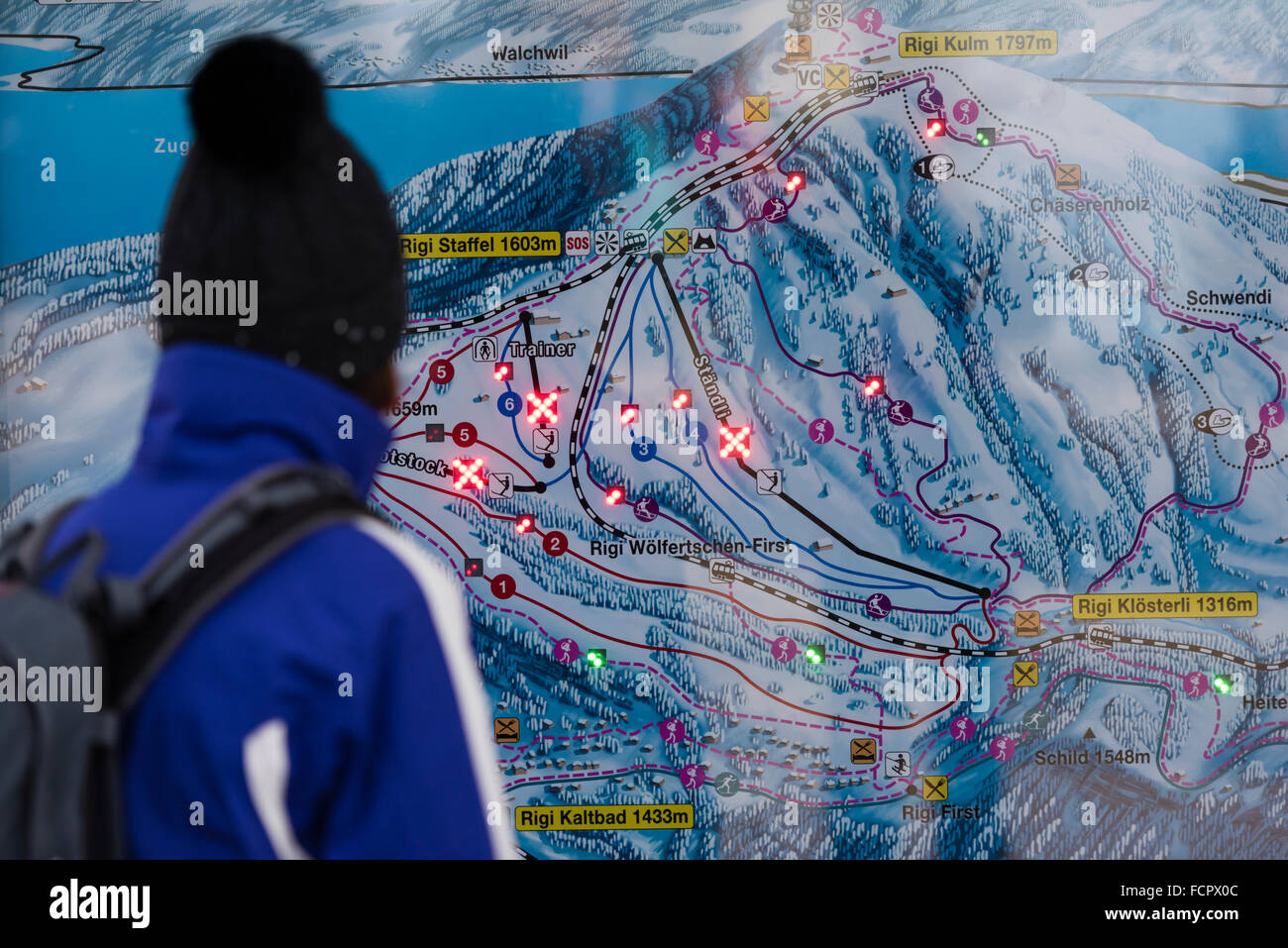 A tourist is checking the map of the ski resort at Mount Rigi, Switzerland, just to find all slopes closed due to - Stock Image
