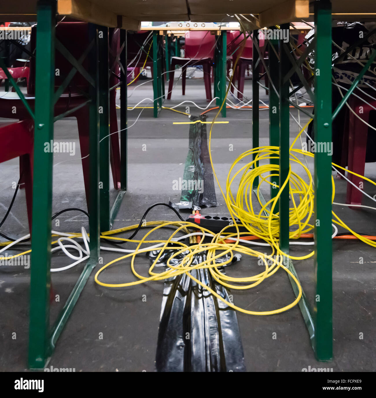 Chaotic computer network cabling under the desks at NetGame computer game convention. - Stock Image
