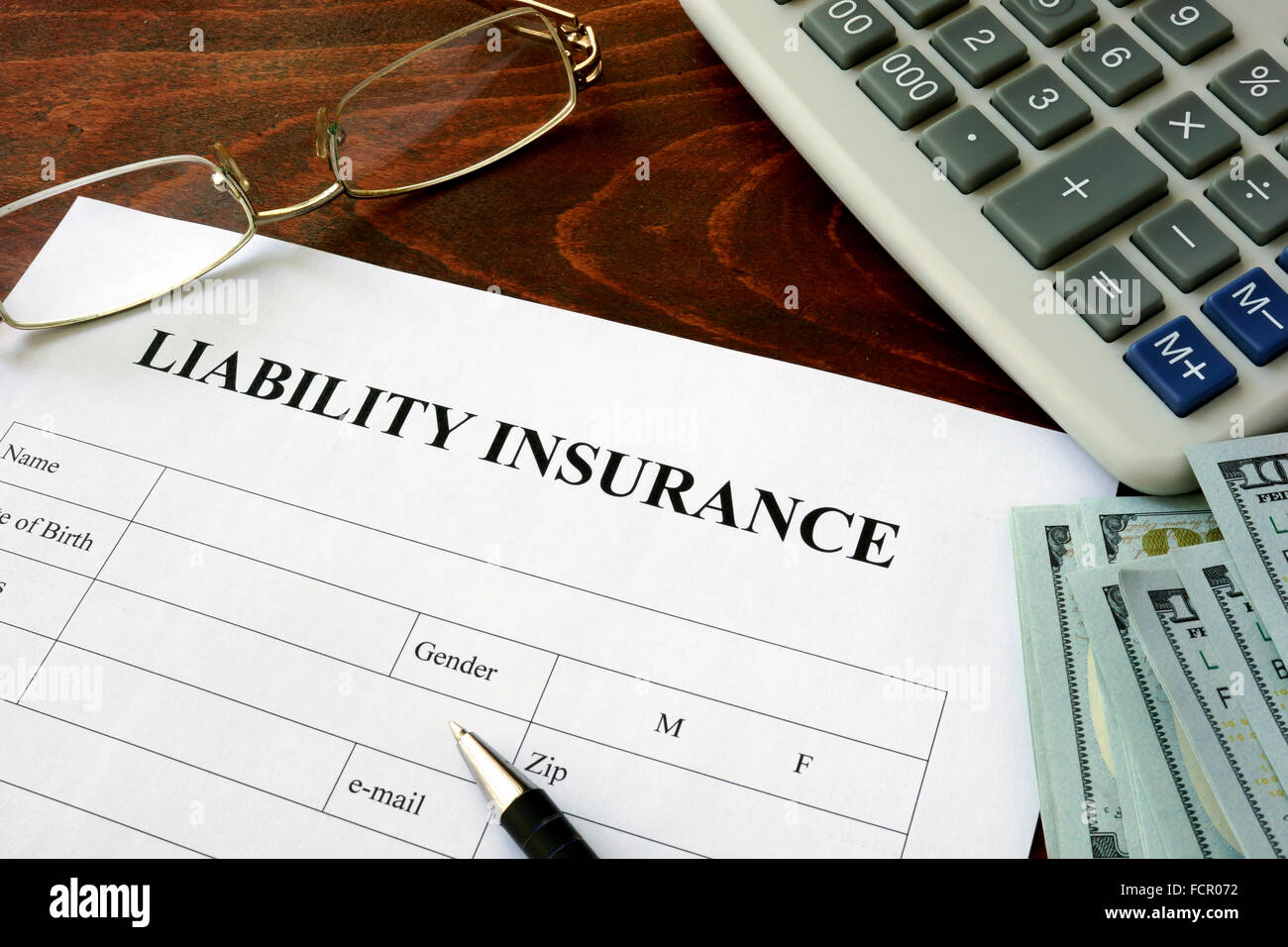 Liability insurance form and dollars on the table. - Stock Image
