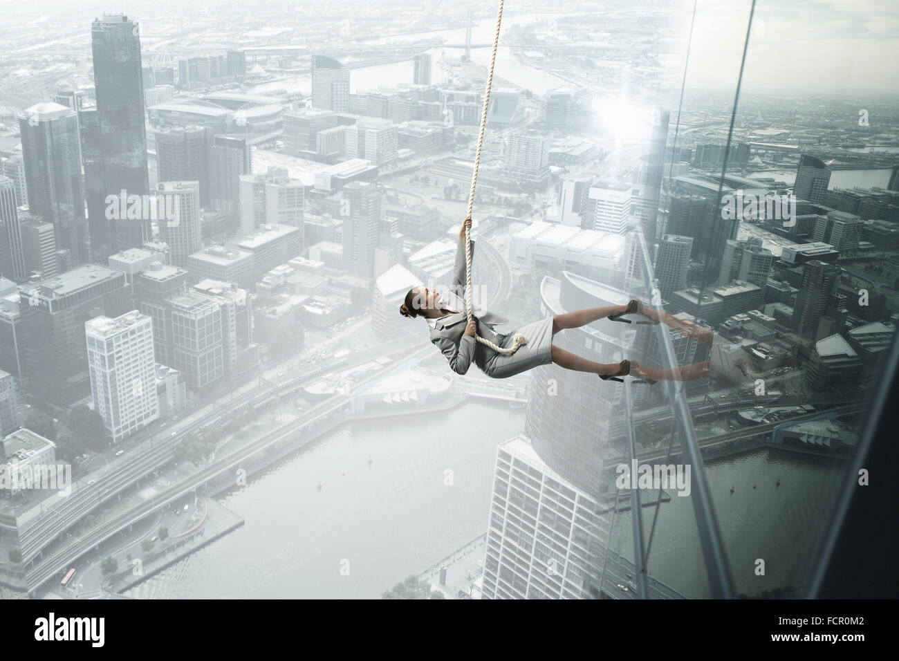 Concept of competition with businesswoman climbing office building with rope - Stock Image