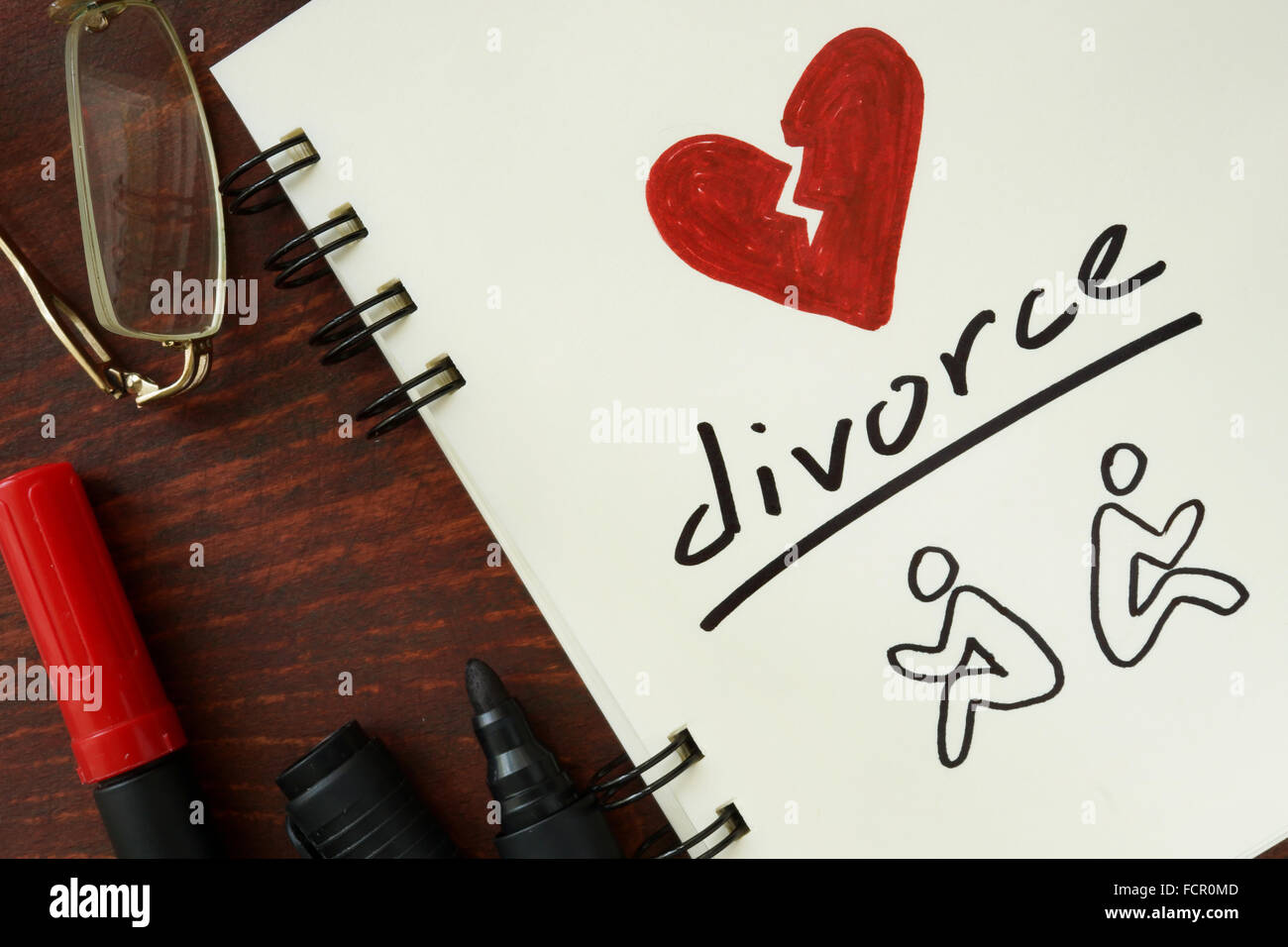 Notepad with divorce on the wooden table. - Stock Image