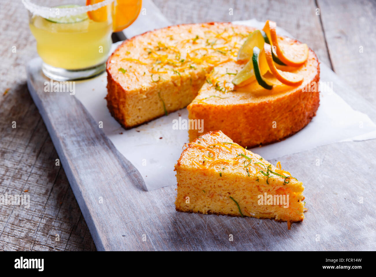 Home made whole testy orange cake on a wooden surface - Stock Image