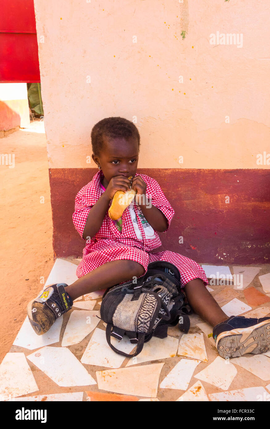 Lunch break for black infant child at a charity run school in the back streets of Kololi Gambia - Stock Image