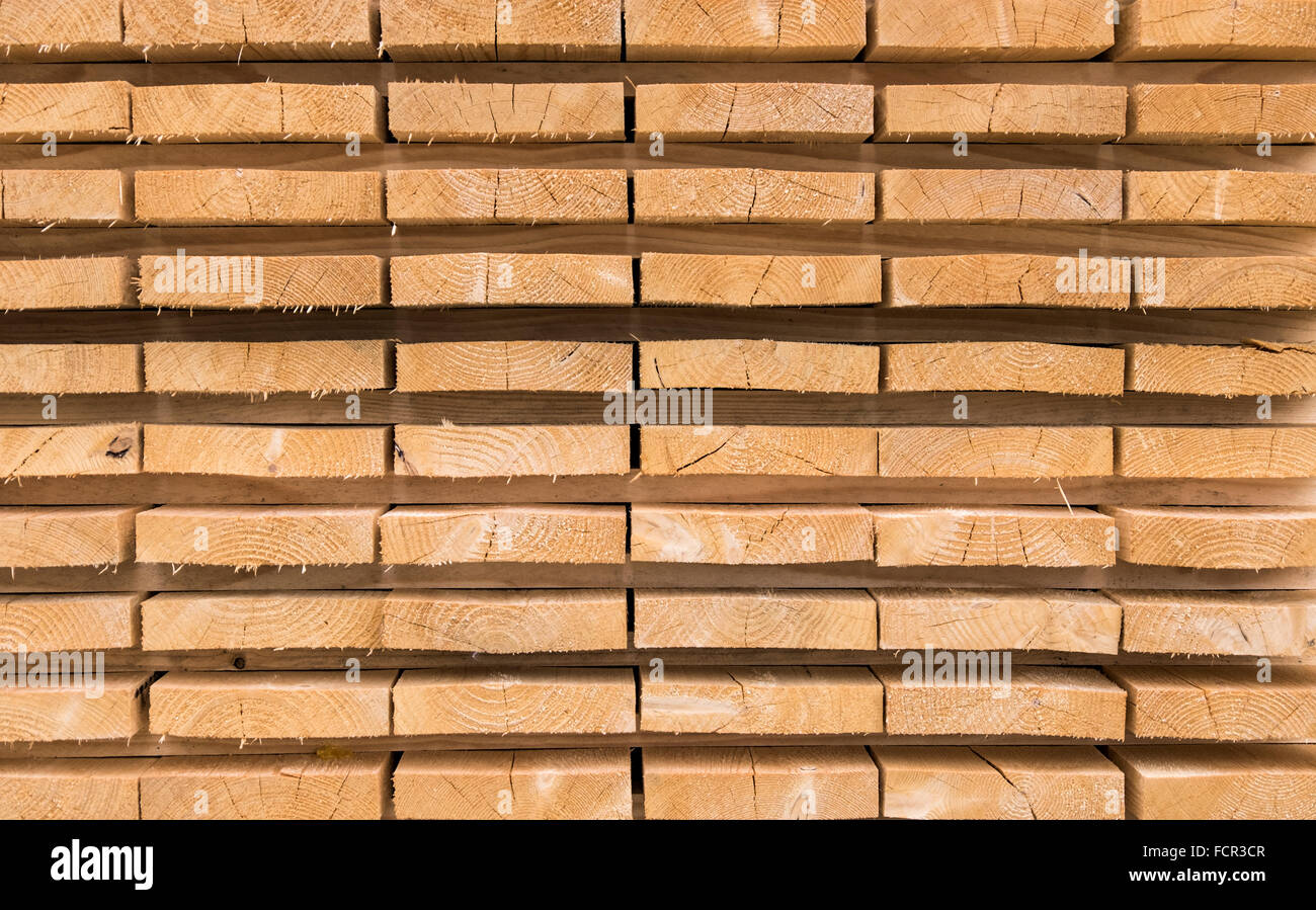 Trimmed and debarked timber planks piled up at a sawmill Stock Photo