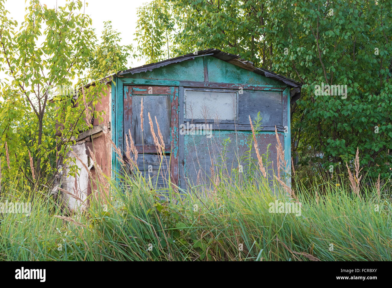 Abandoned garden house surrounded by trees and grass. Shooting at dawn. - Stock Image
