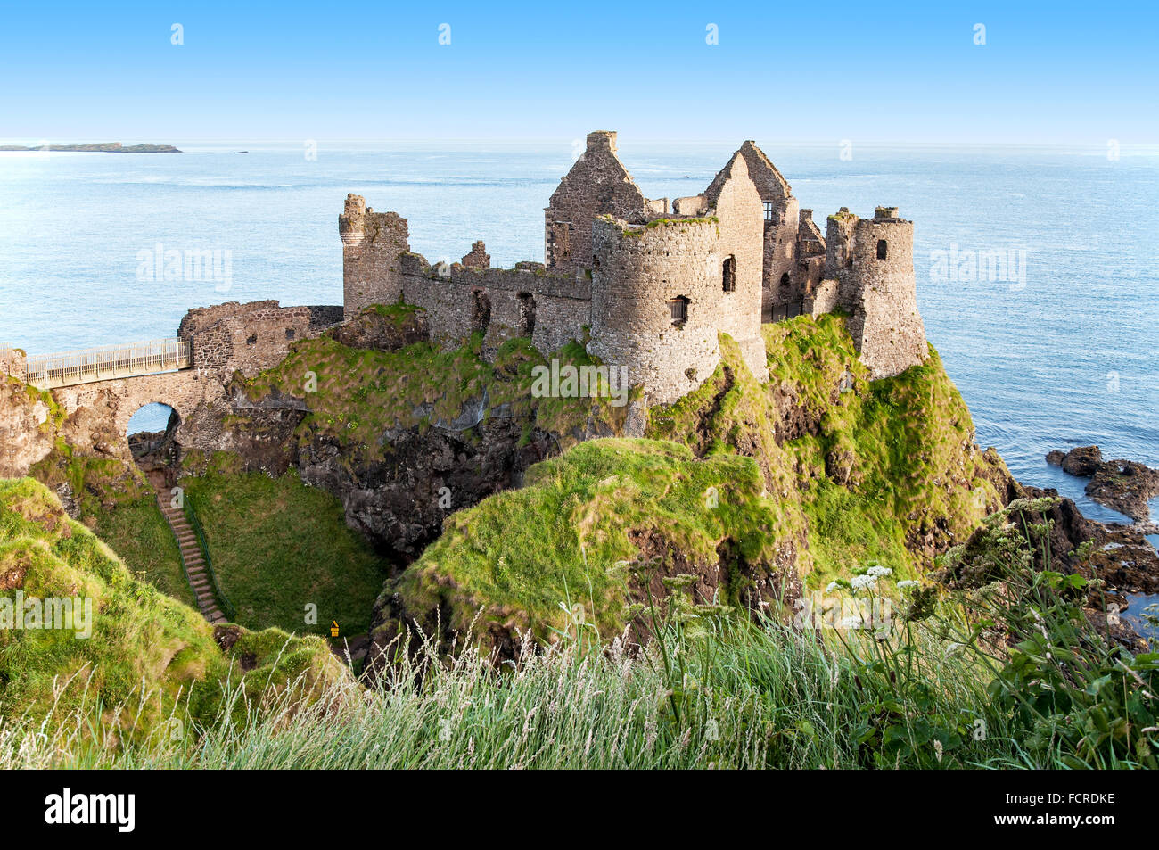 Ruins of medieval Dunluce Castle, County Antrim, Northern Ireland, at sunrise light - Stock Image