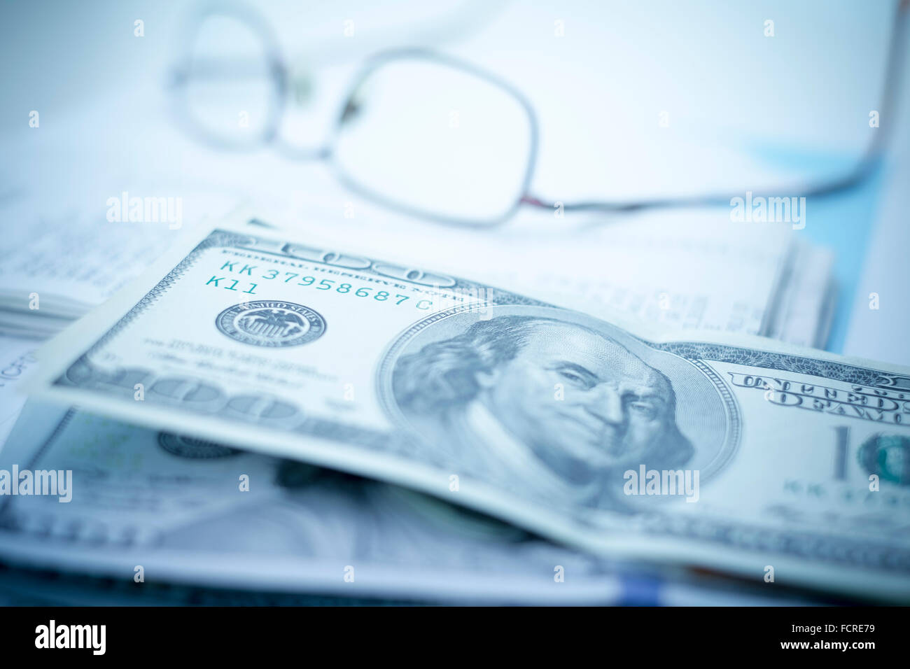 Glasses with money and receipts on a desk - Stock Image
