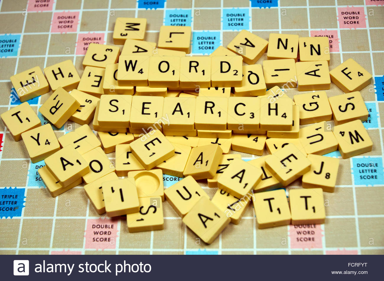 A mixed pile of scrabble letters spelling out the phrase of word search - Stock Image