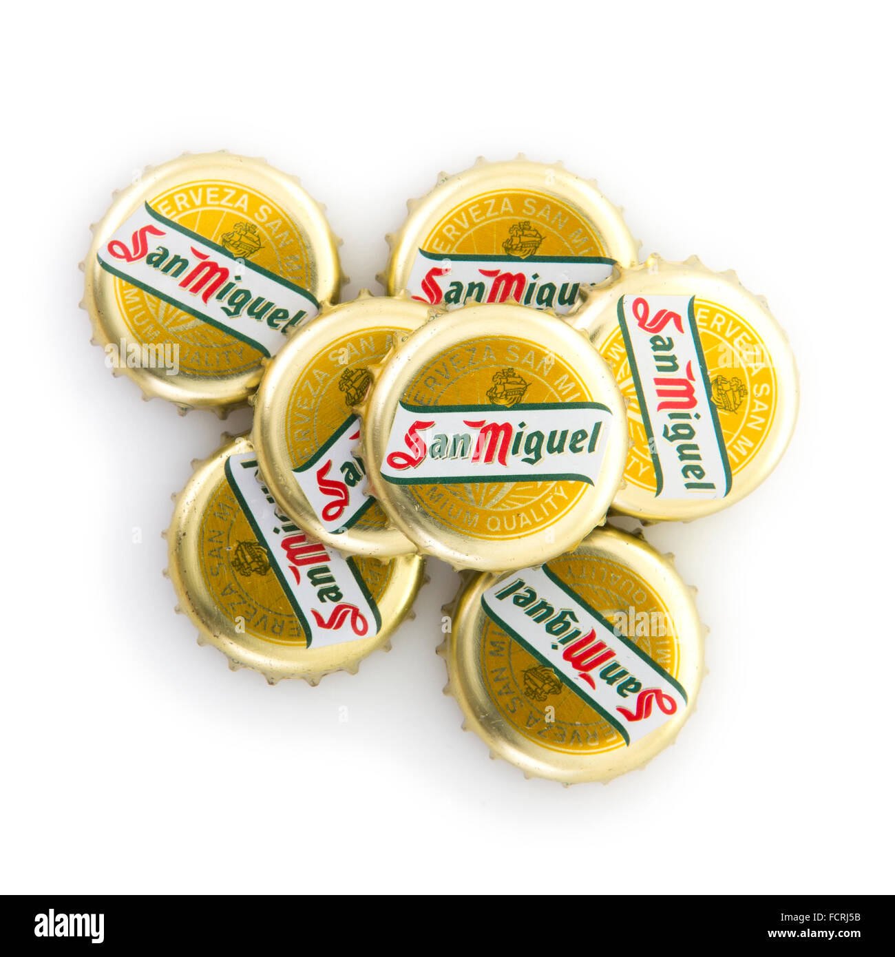 San Miguel beer bottle caps on white background - Stock Image
