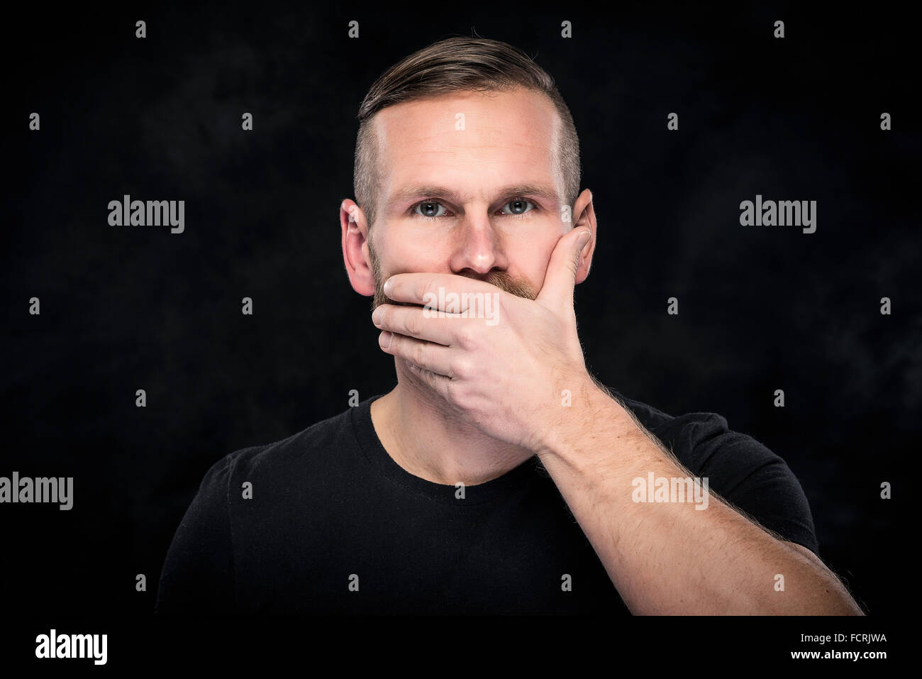 Man with hand covering his mouth. - Stock Image