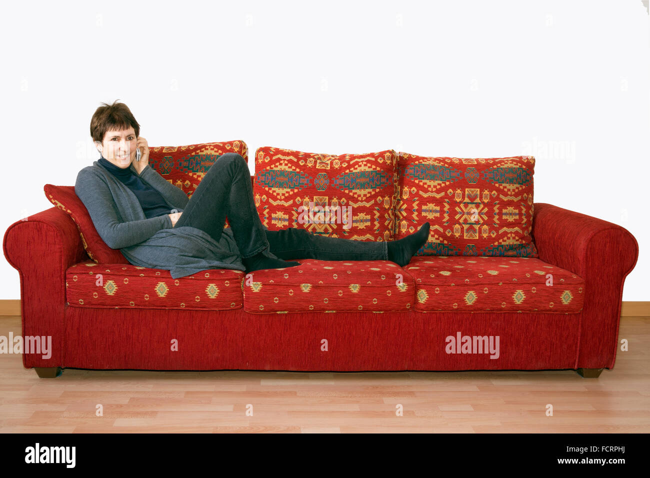 Older woman gossiping on phone, on sofa. - Stock Image