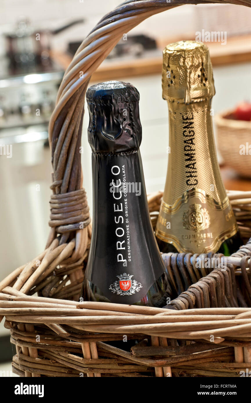 Prosecco and Champagne bottles in wicker bottle carrier, standing in contemporary home kitchen situation Sparkling - Stock Image