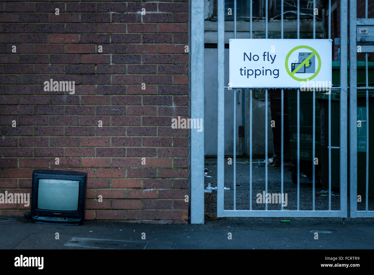 A TV dumped feet from a 'No fly tipping' sign - Stock Image