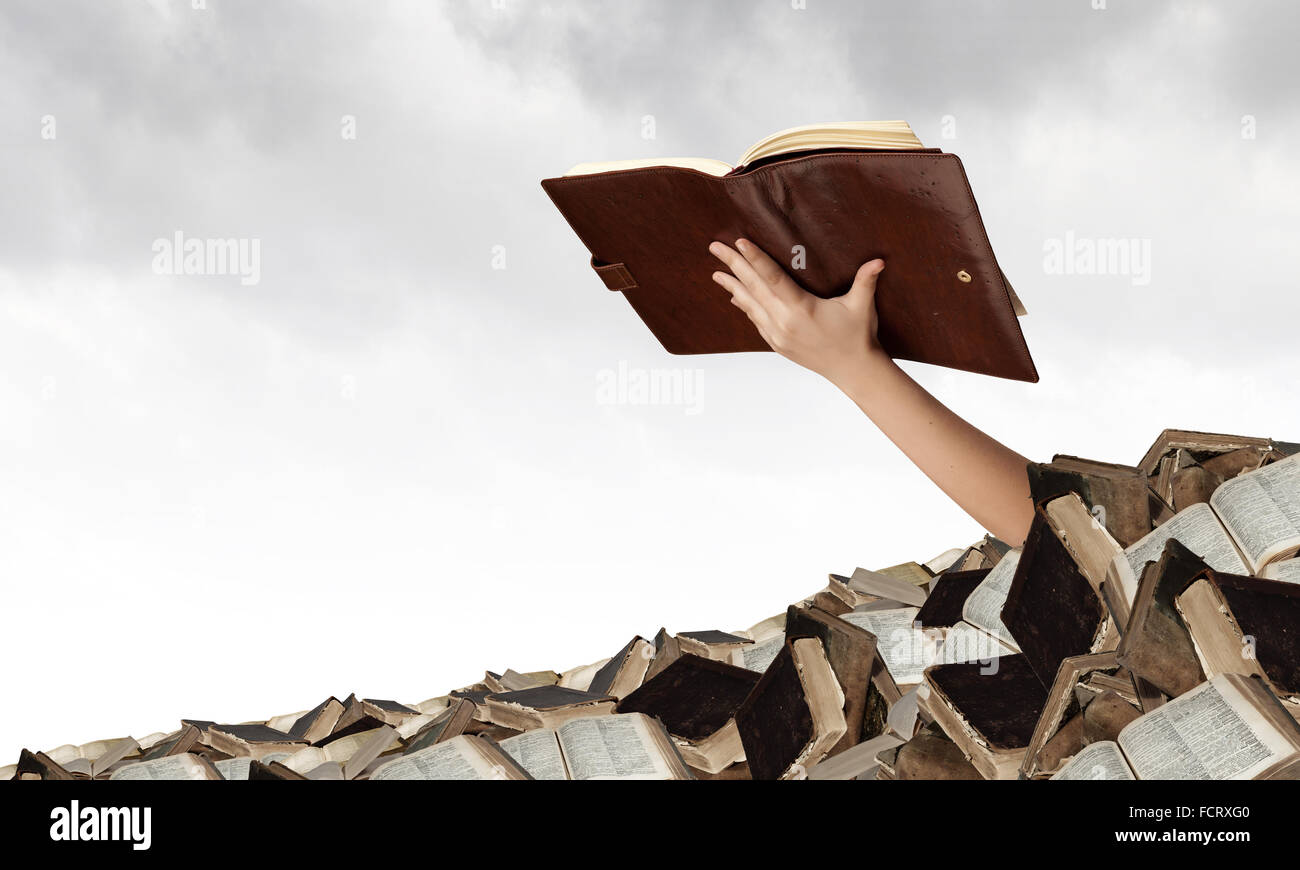 Hand with book reaching out from pile of old books - Stock Image