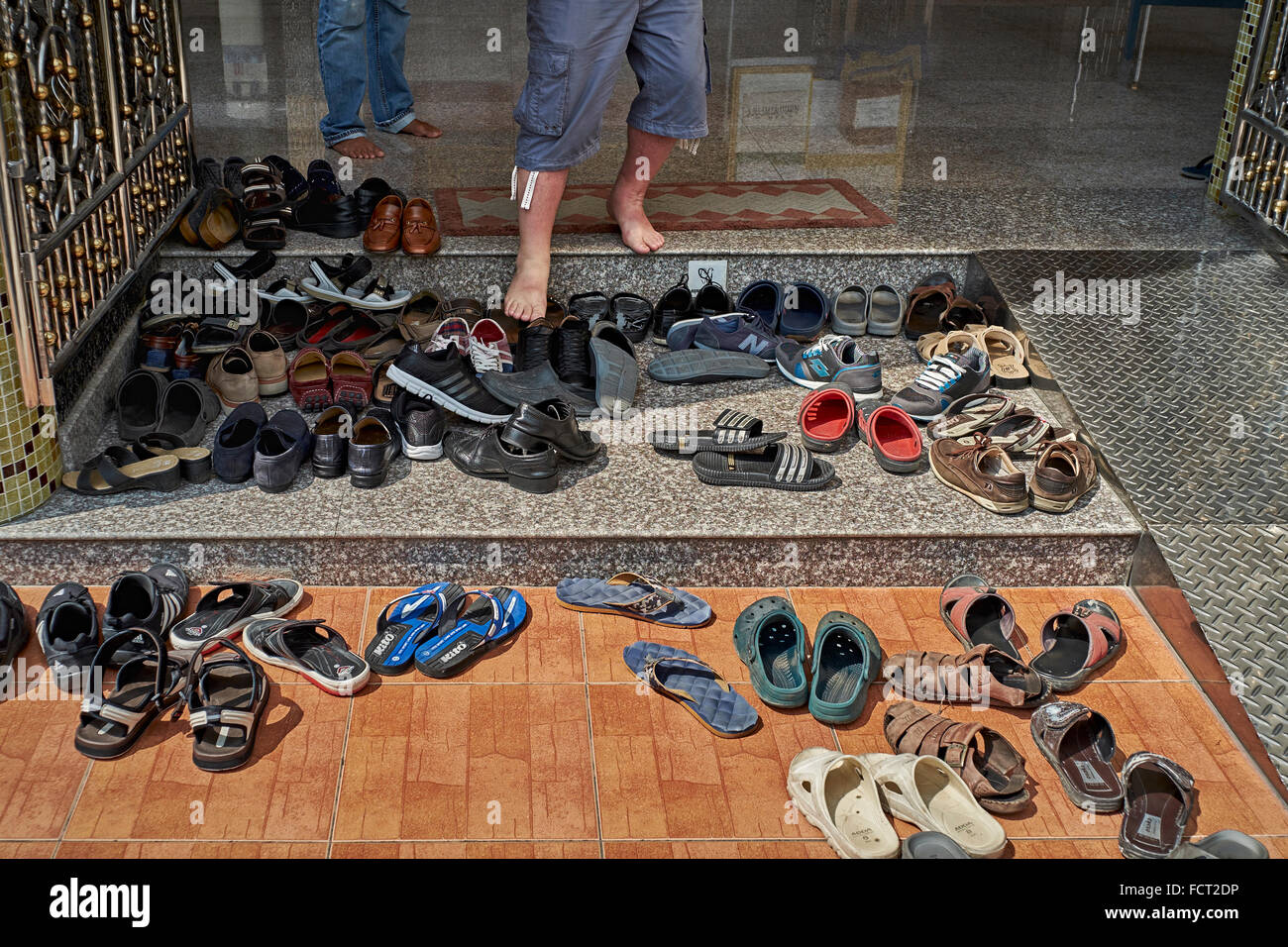 Asian tradition of removing footwear before entering premises. Array of shoes outside a Thailand temple. - Stock Image