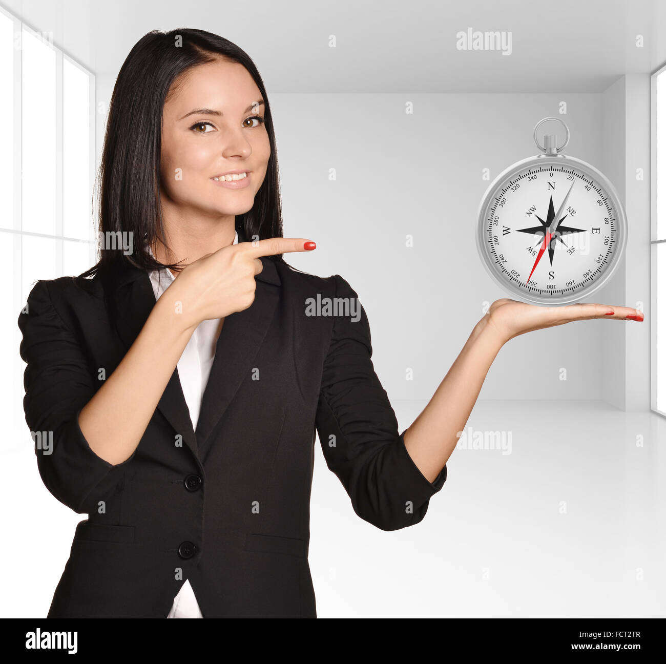 Office girl standing on background of light interior and holding compass Stock Photo