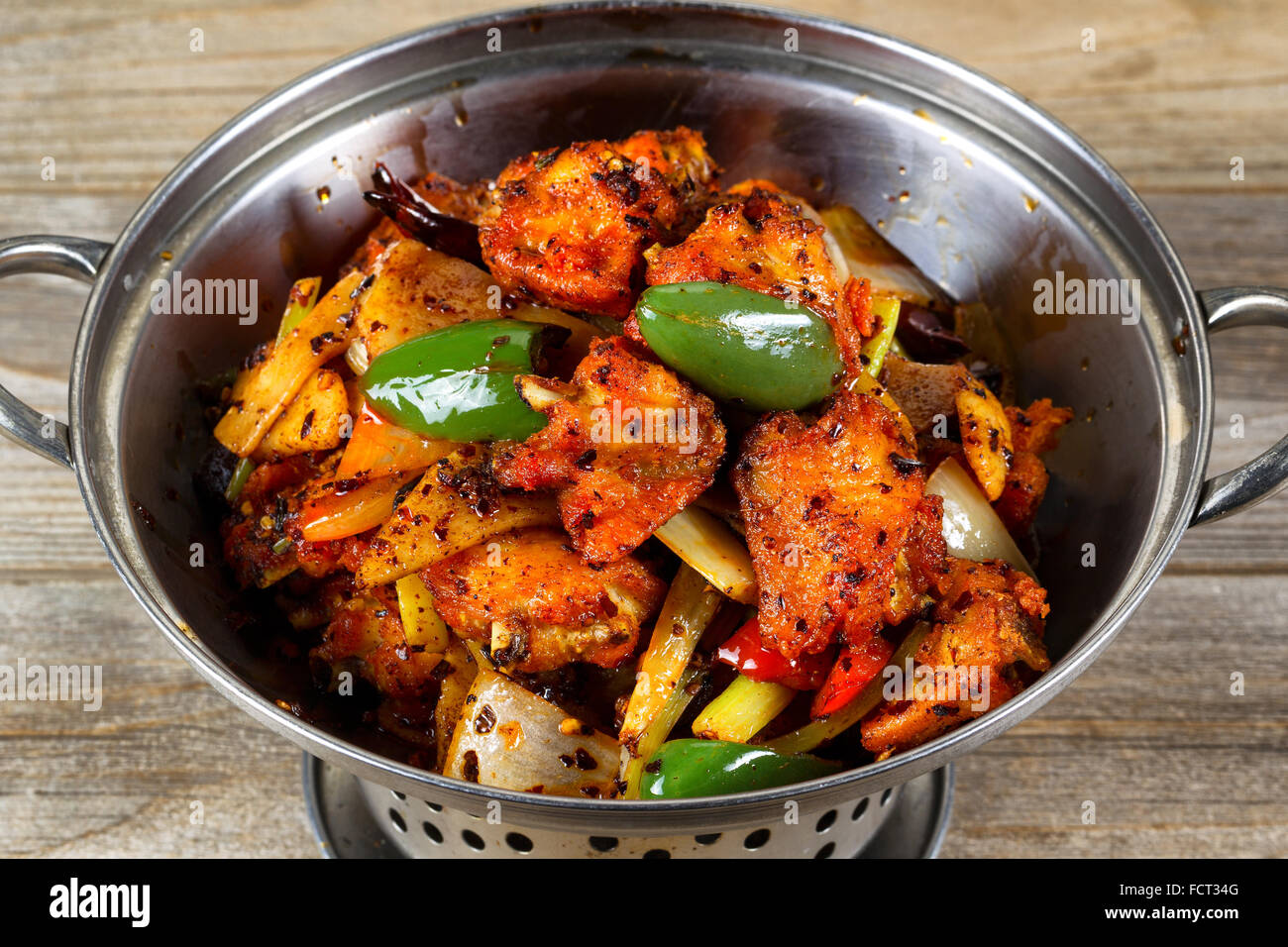 High angled view of a stainless steel cooking pot filled fried chicken and vegetables on rustic wood. - Stock Image