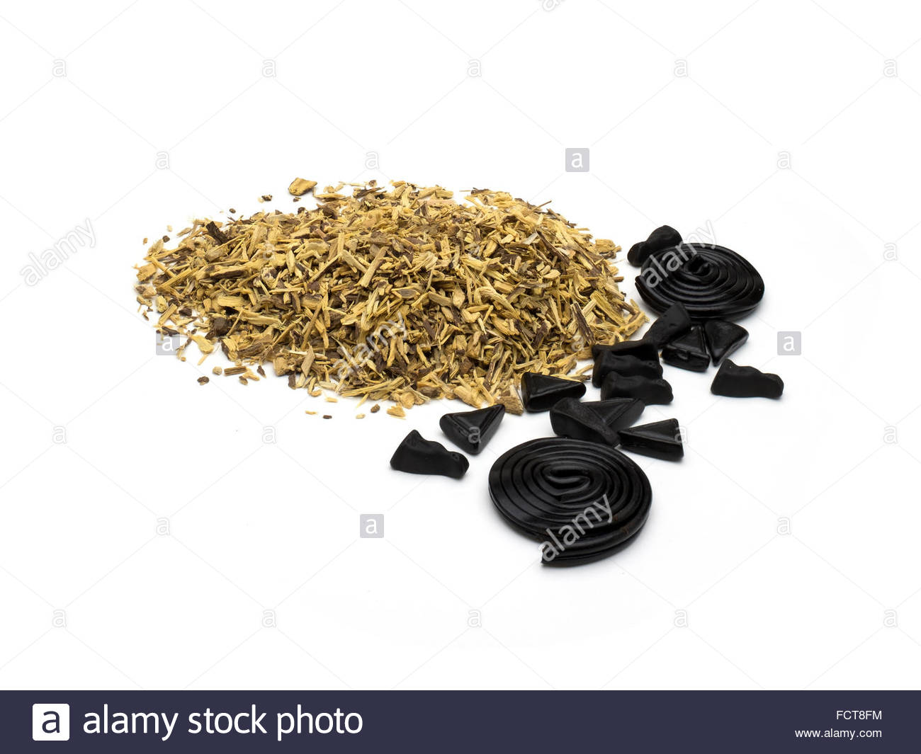 Liquorice (licorice), Glycyrrhiza glabra, with candy made from it. - Stock Image