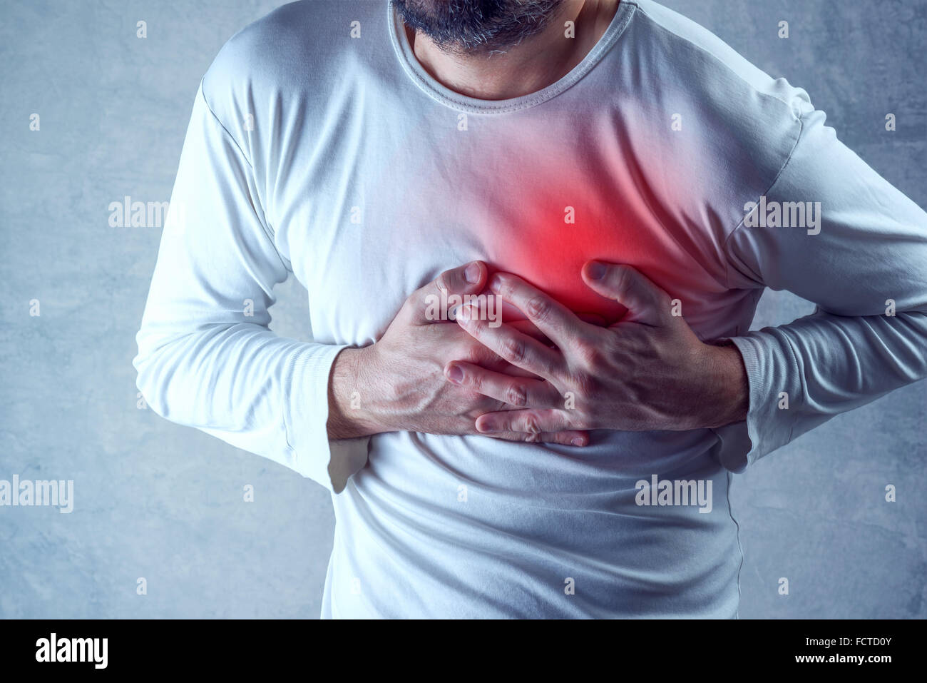 Severe heartache, man suffering from chest pain, having heart attack or painful cramps, pressing on chest - Stock Image