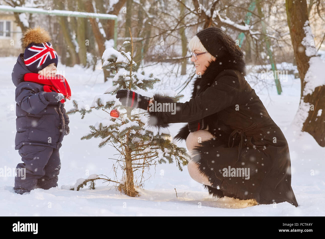 woman with her son decorating christmas pine - Stock Image