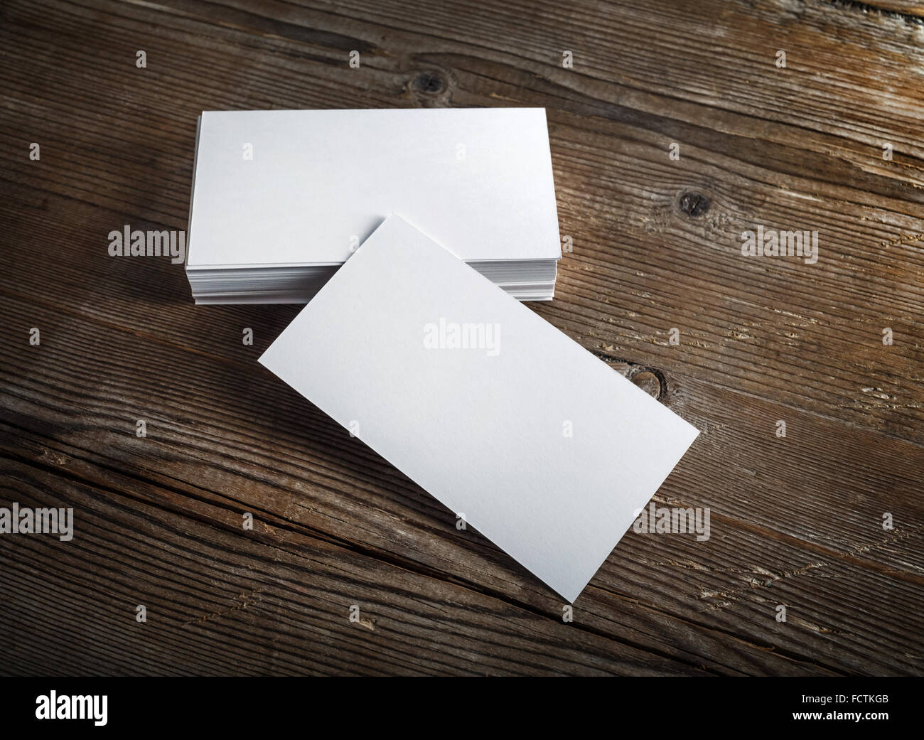 blank white business cards on a dark wooden background mockup for