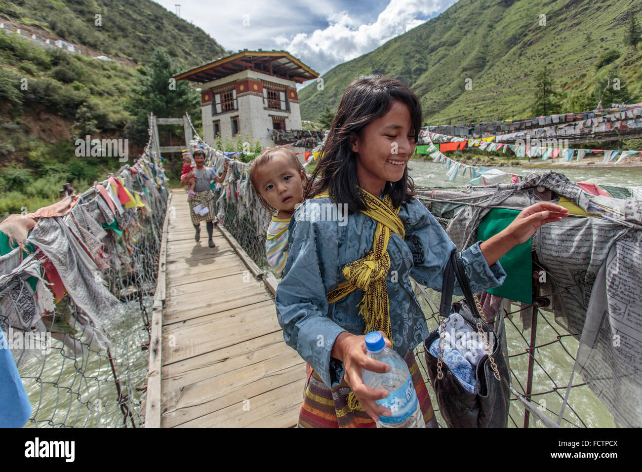 Mother and child crossing a suspension bridge near Thimphu, Bhutan - Stock Image