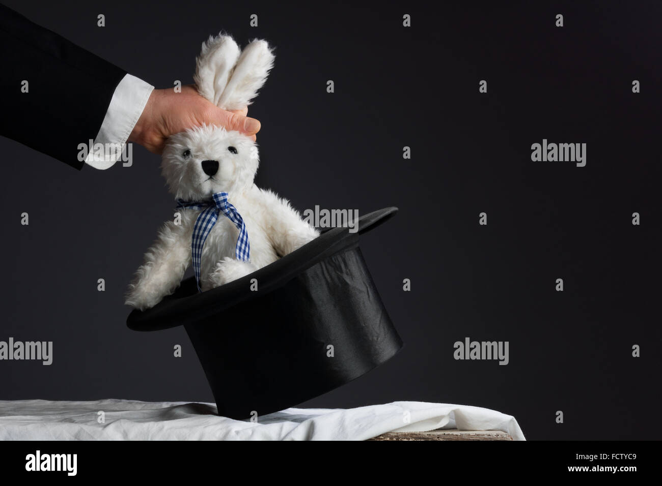 Man in suit pulling a rabbit out of the topper hat - Stock Image