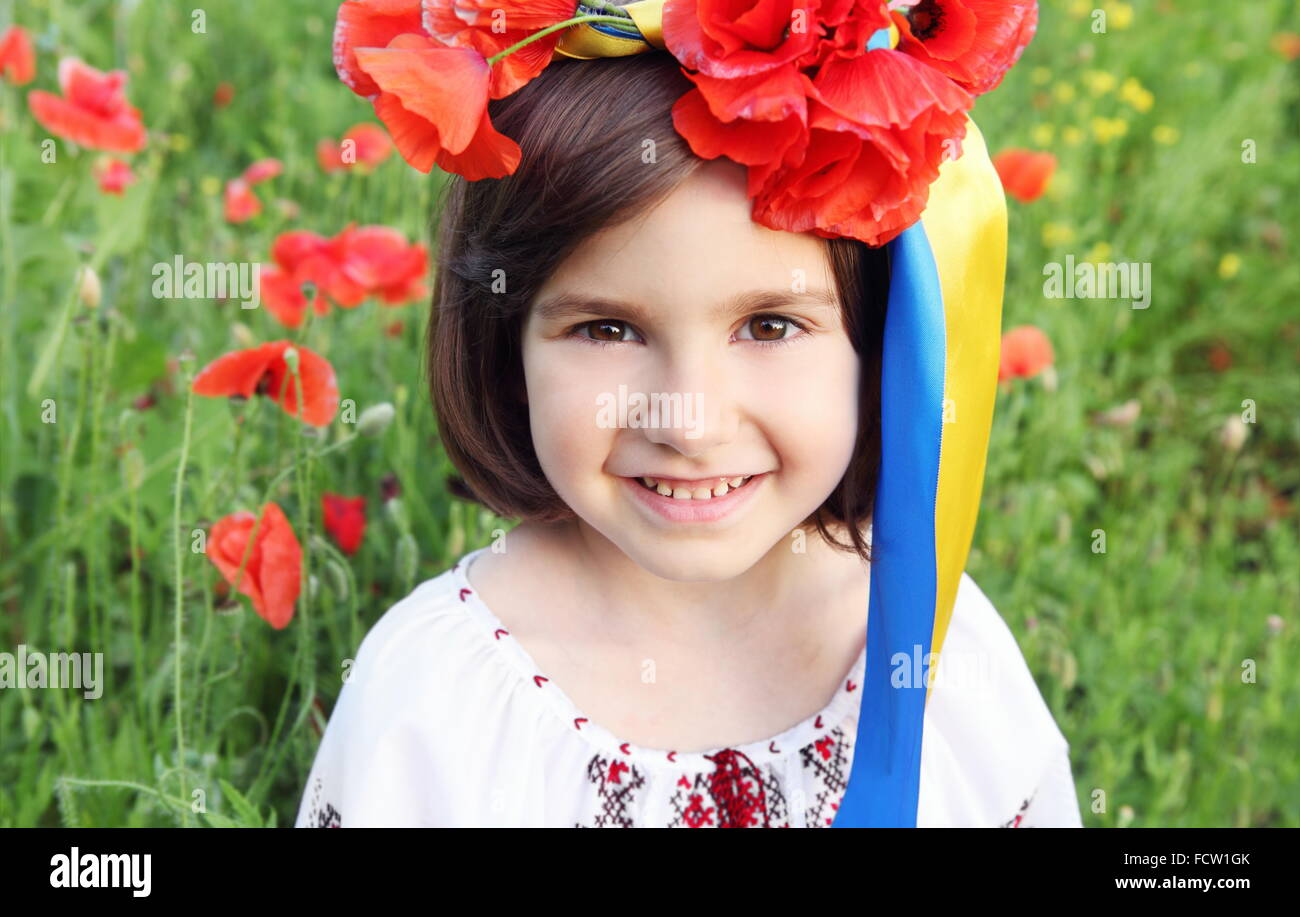 Girl on Poppy Meadow in Wreath with Ukrainian Flag Colors Ribbons - Stock Image