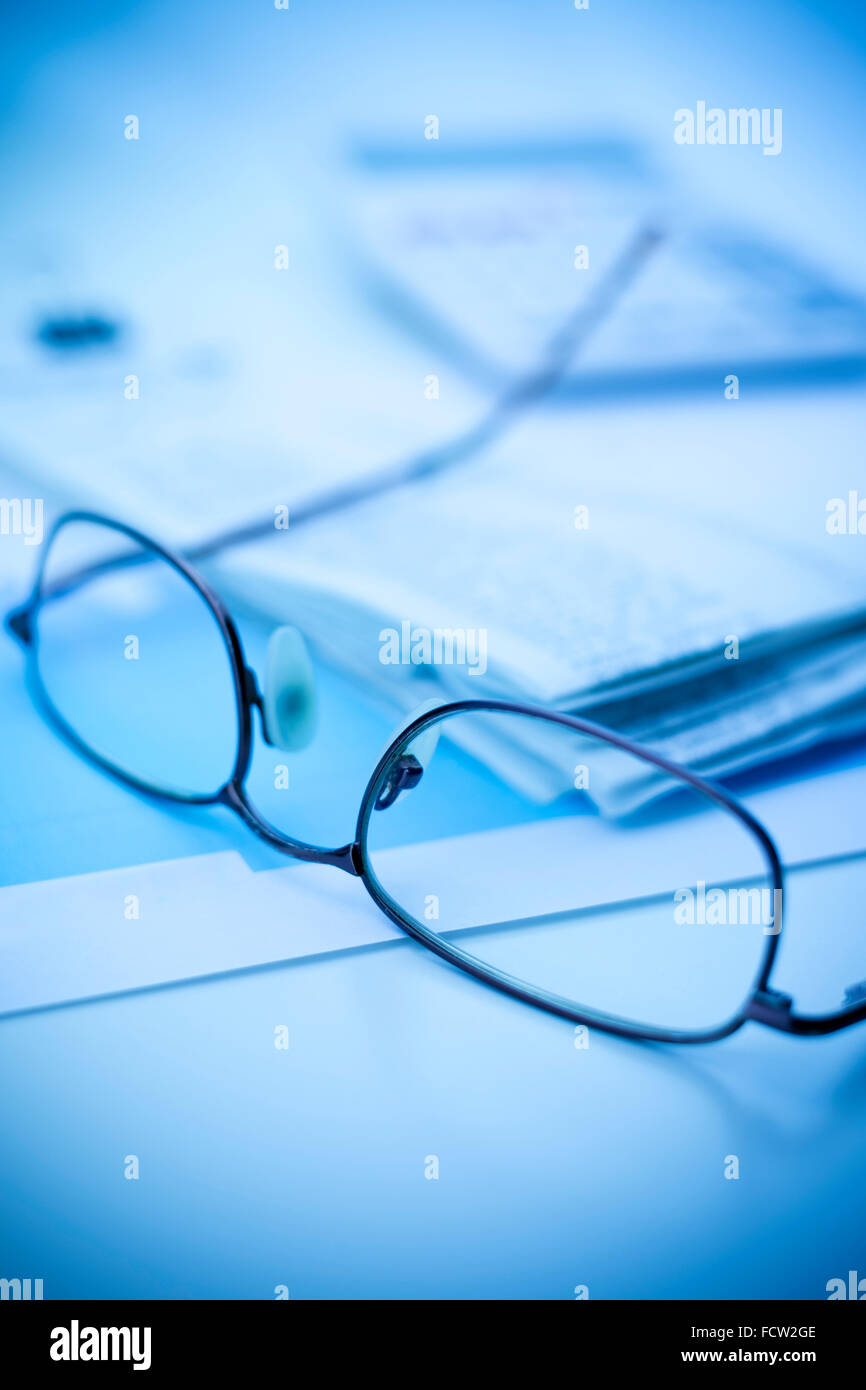 Glasses with a calculator and receipts on a desk - Stock Image