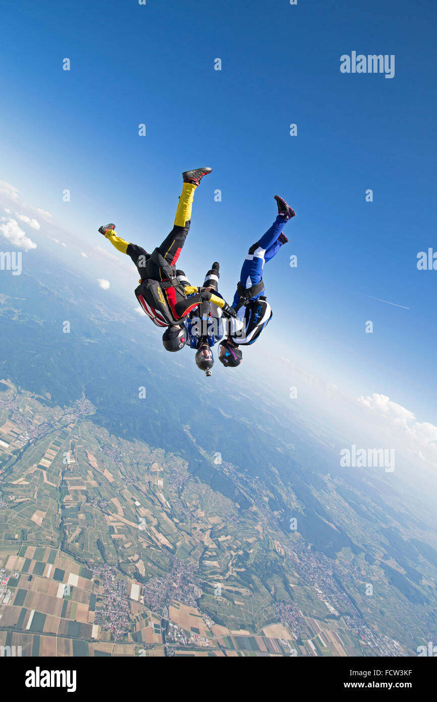 This freefly skydiving team is holding hand in a head-down position. Thereby they rush with a speed over 150 mph - Stock Image