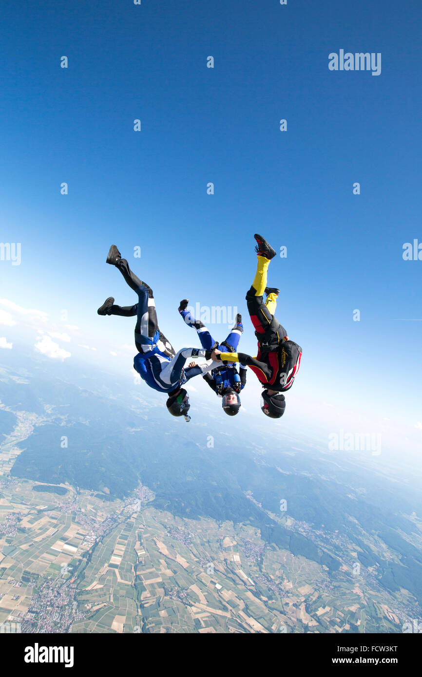 This freefly skydiving team is holding hand together in a head-down position. Thereby they rush with a speed over - Stock Image