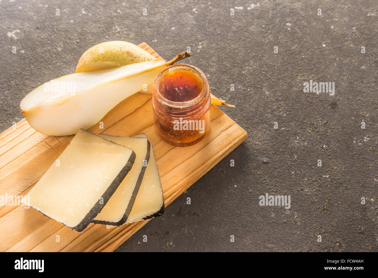 A composition of italian cheese pecorino slices with jam and pears on a wooden chopping board - Stock Image