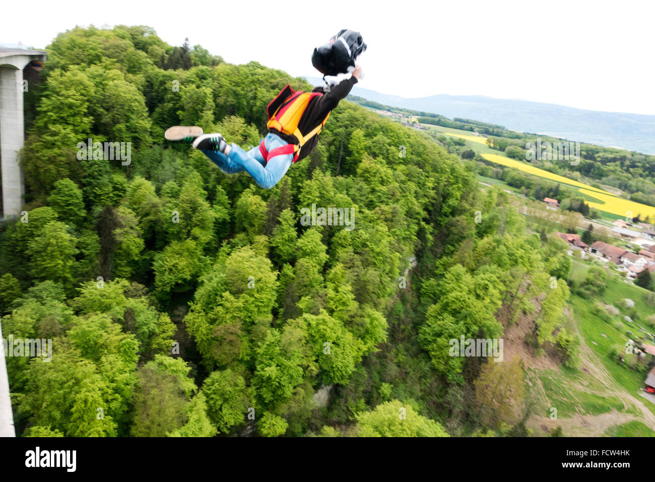 Man is exiting from a bridge with his BASE jumping equipment. With the pilot-chute in his hand he'll forces - Stock Image