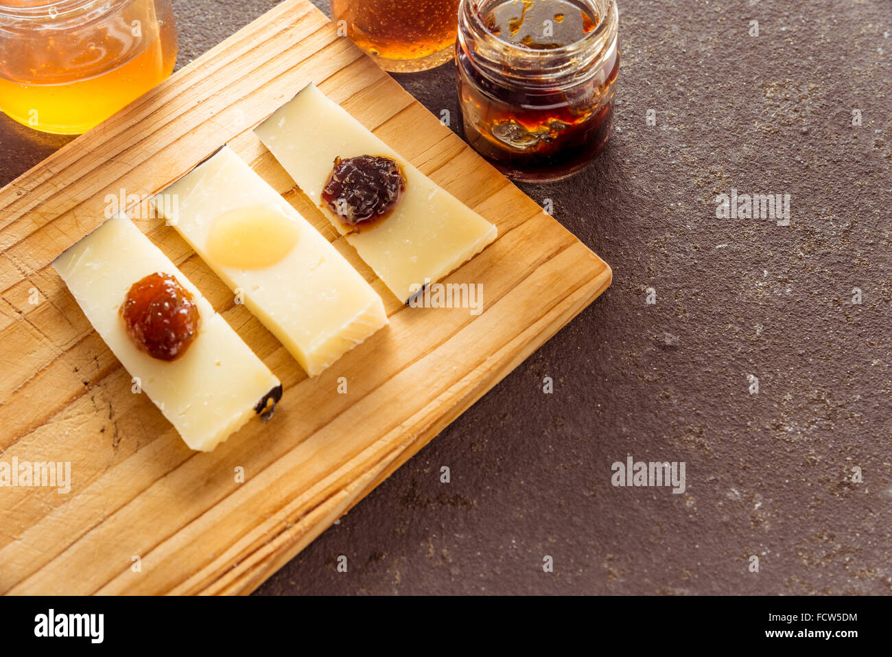 A composition of italian cheese pecorino slices with jams of different flavours on a wooden chopping board - Stock Image