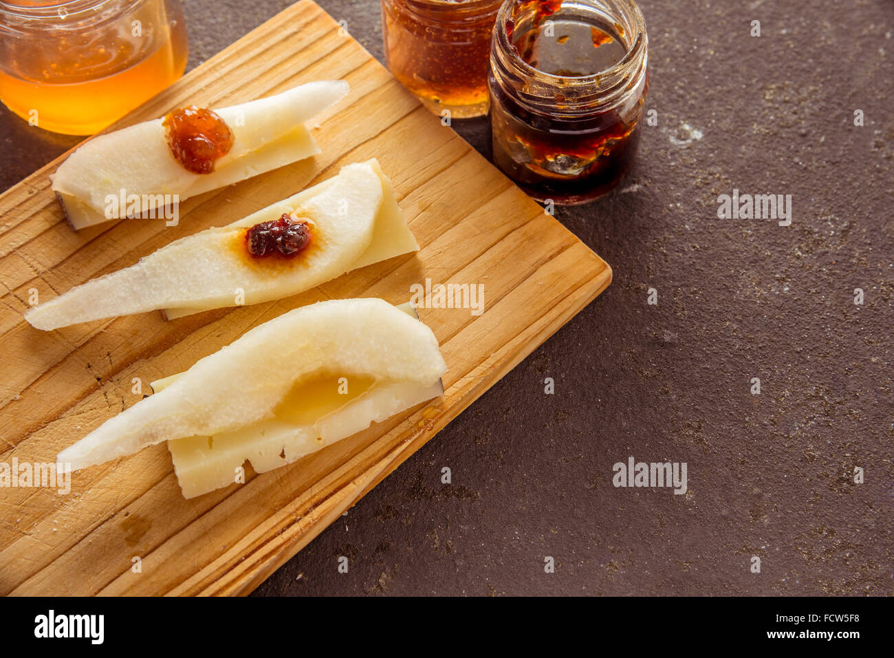 A composition of italian cheese pecorino slices with jams and pears on a wooden chopping board - Stock Image
