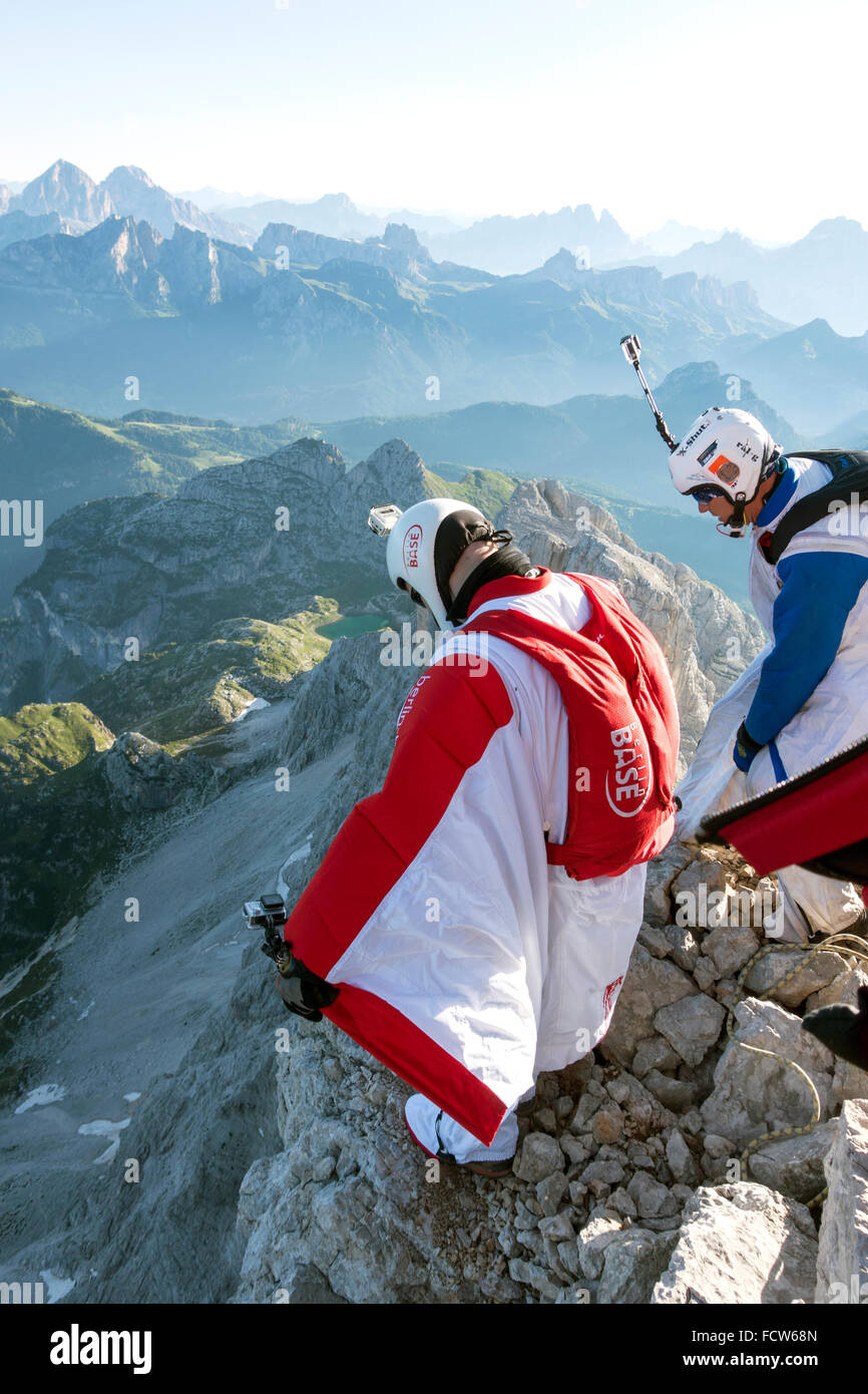 These two BASE jumpers are getting ready to exit from a cliff. Just a last check before they'll spread their - Stock Image
