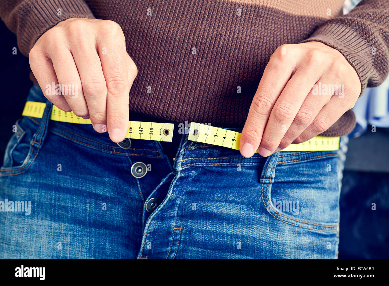 a young man with a measuring tape as a belt tries to fasten his trousers, because of the weight gain - Stock Image