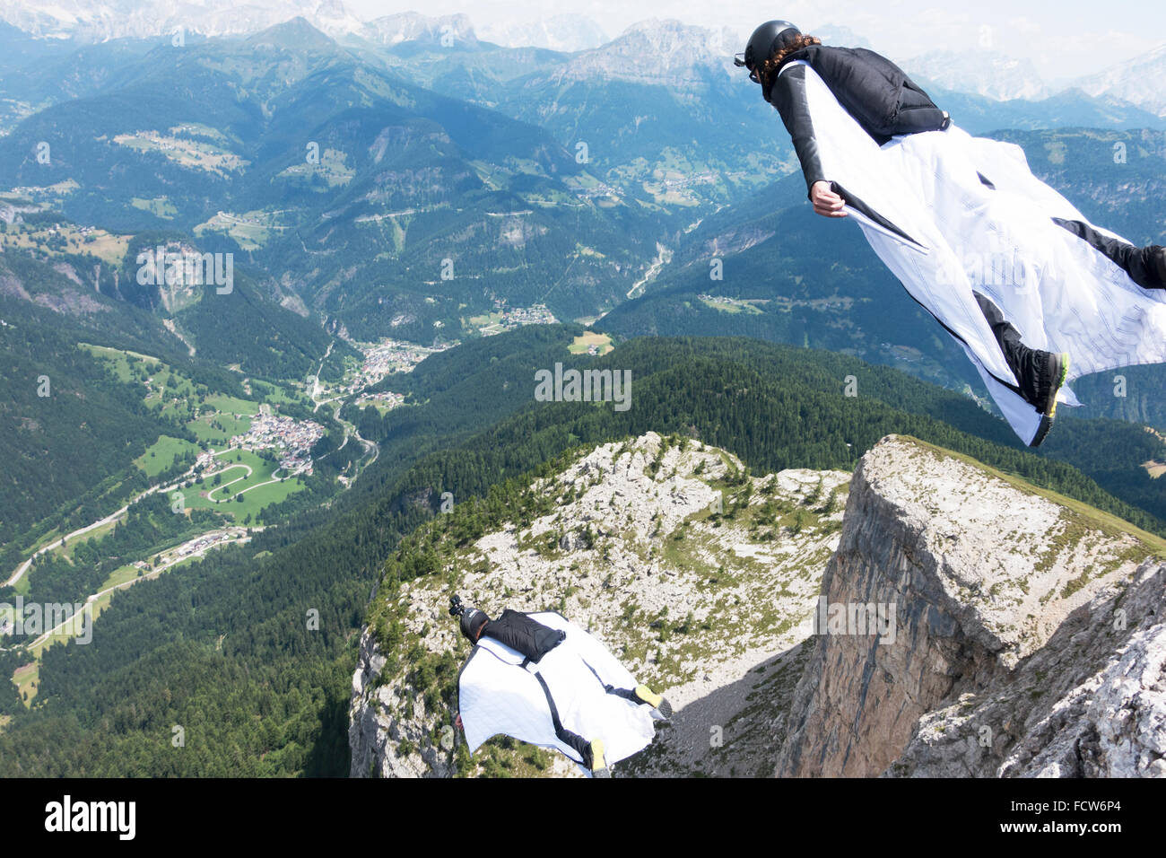These two Wingsuit BASE jumpers just exit from a cliff. Soon they'll fly together in a formation and soar along - Stock Image