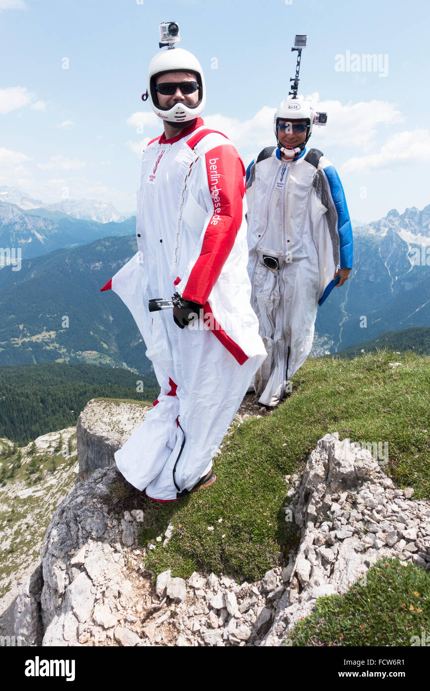 These two BASE jumpers are getting ready to exit from a cliff. Just a last smile before they'll spread their - Stock Image