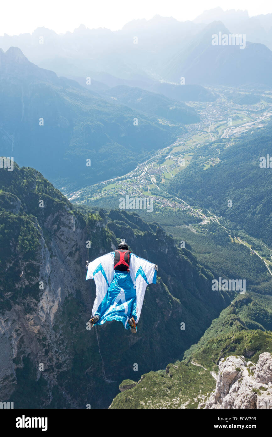 This Wingsuit BASE jumper is soaring down the valley along some cliffs. Thereby he feels the adrenaline rush in - Stock Image