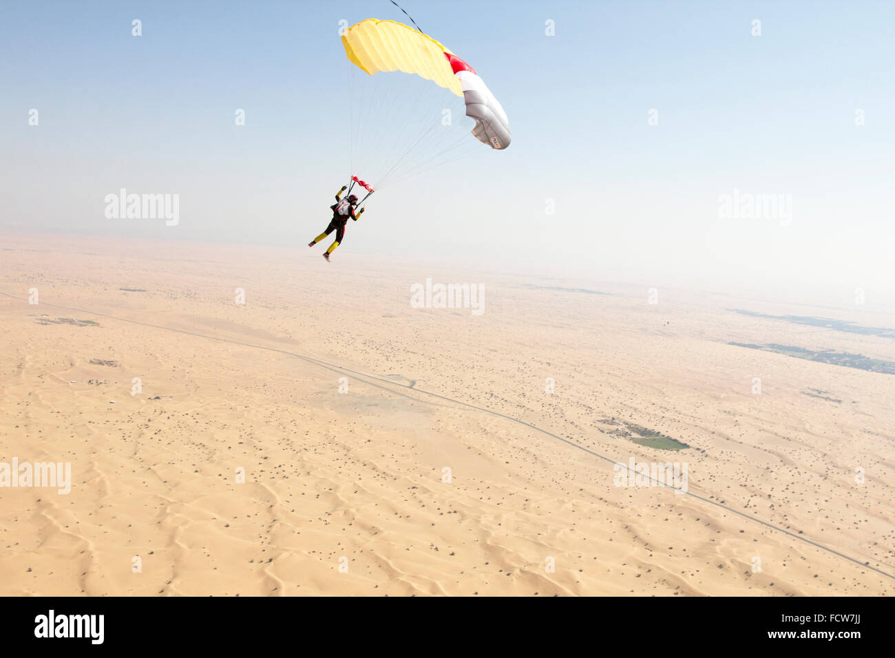 This skydiver girl is flying under his parachute over the Dubai desert area. Thereby she's enjoying the view - Stock Image
