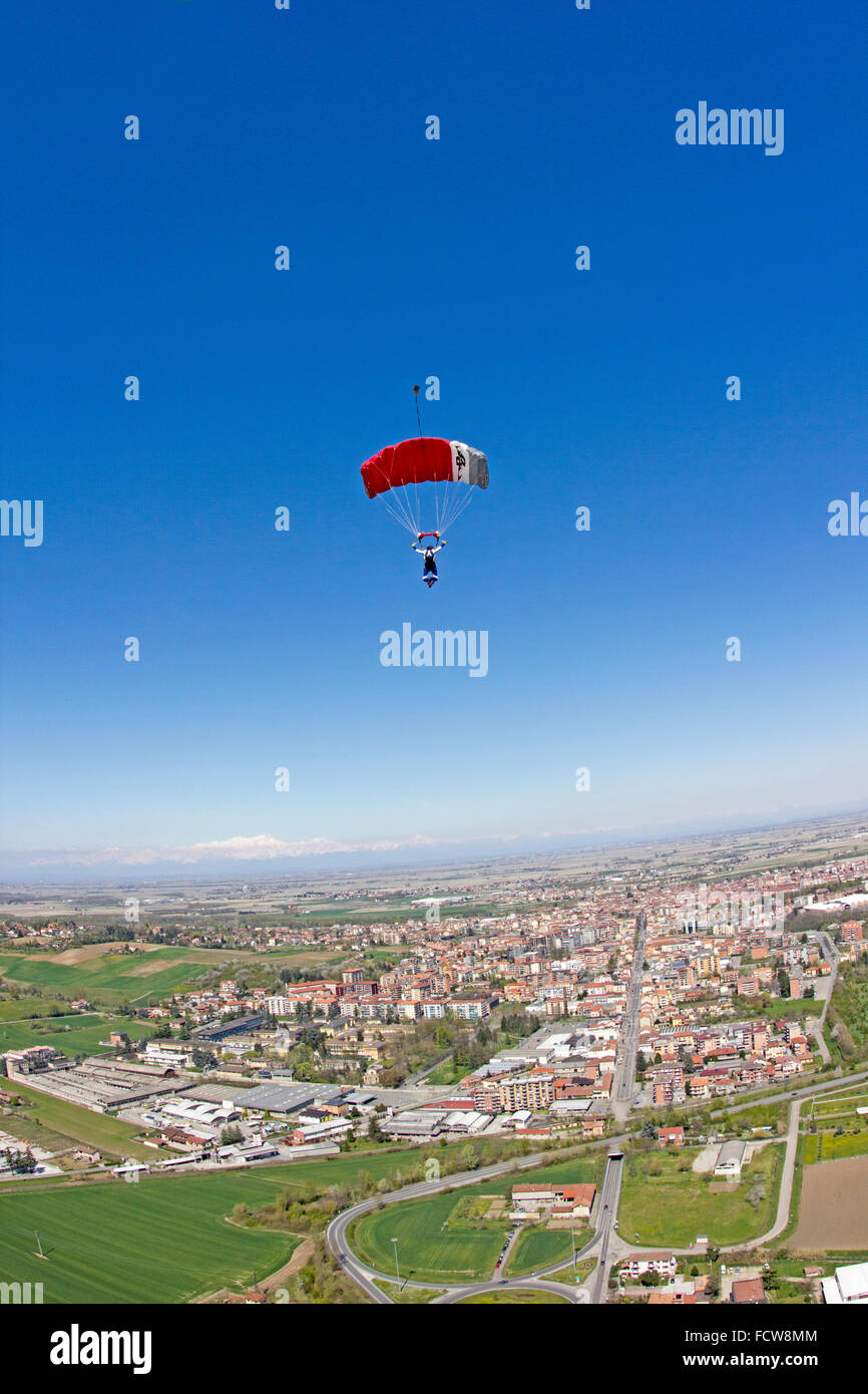 Parachute jumper is flying under his canopy over a city in Italy. Thereby he's looking out for the dedicated - Stock Image
