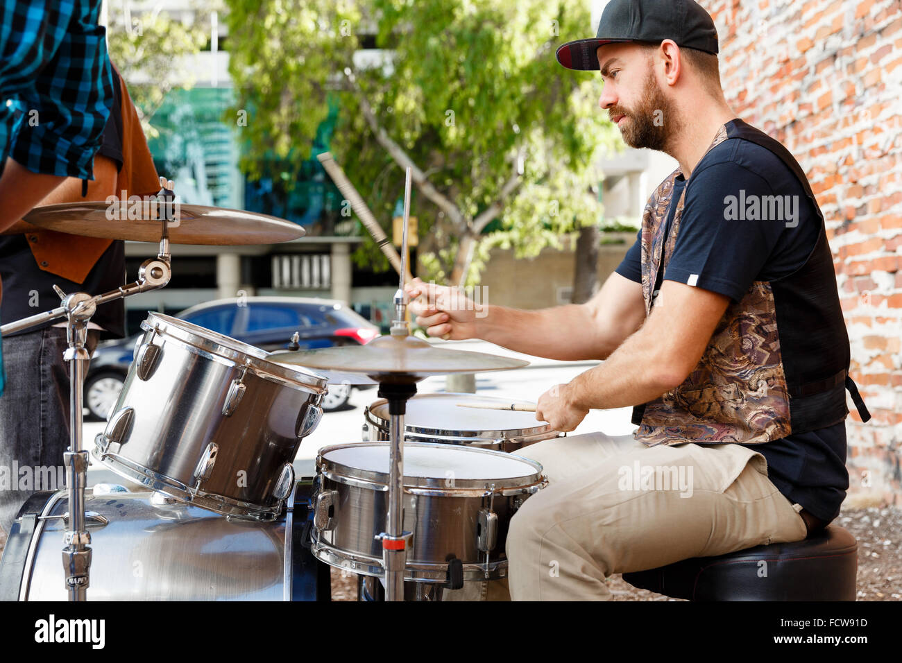 A street muscian playing drums - Stock Image