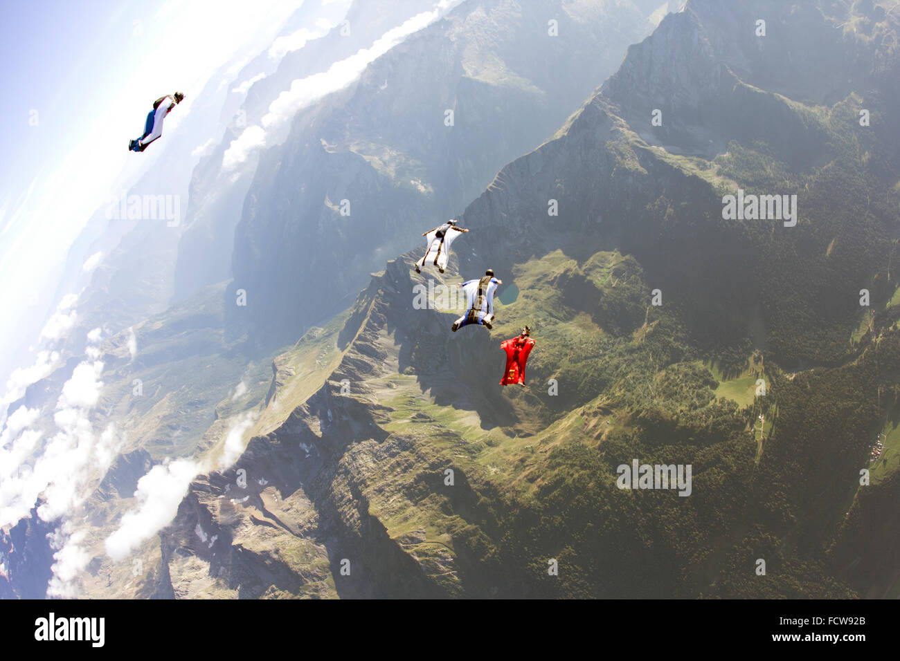 Wingsuit pilots are flying in a group together. The leader in the red suit is flying ahead and guiding them over - Stock Image
