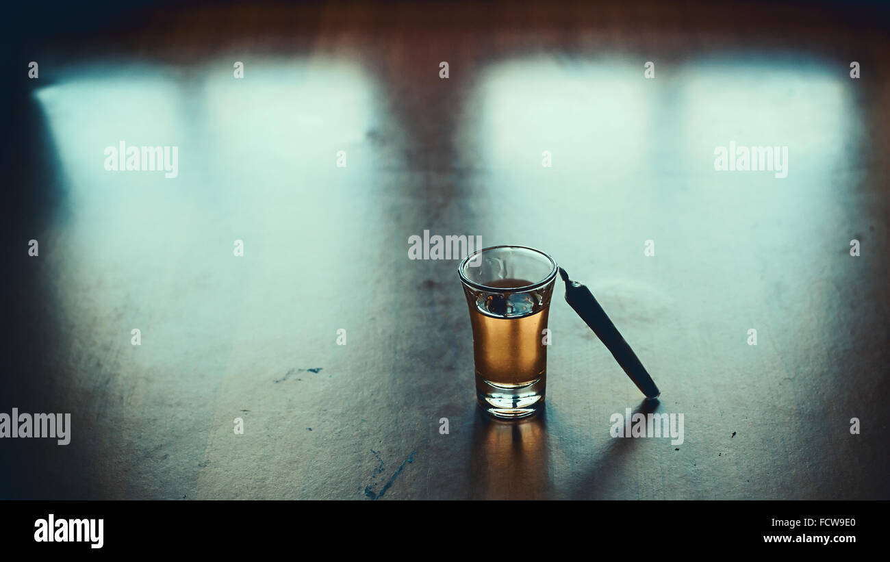 Small glass of spirit drink and one joint on table. - Stock Image