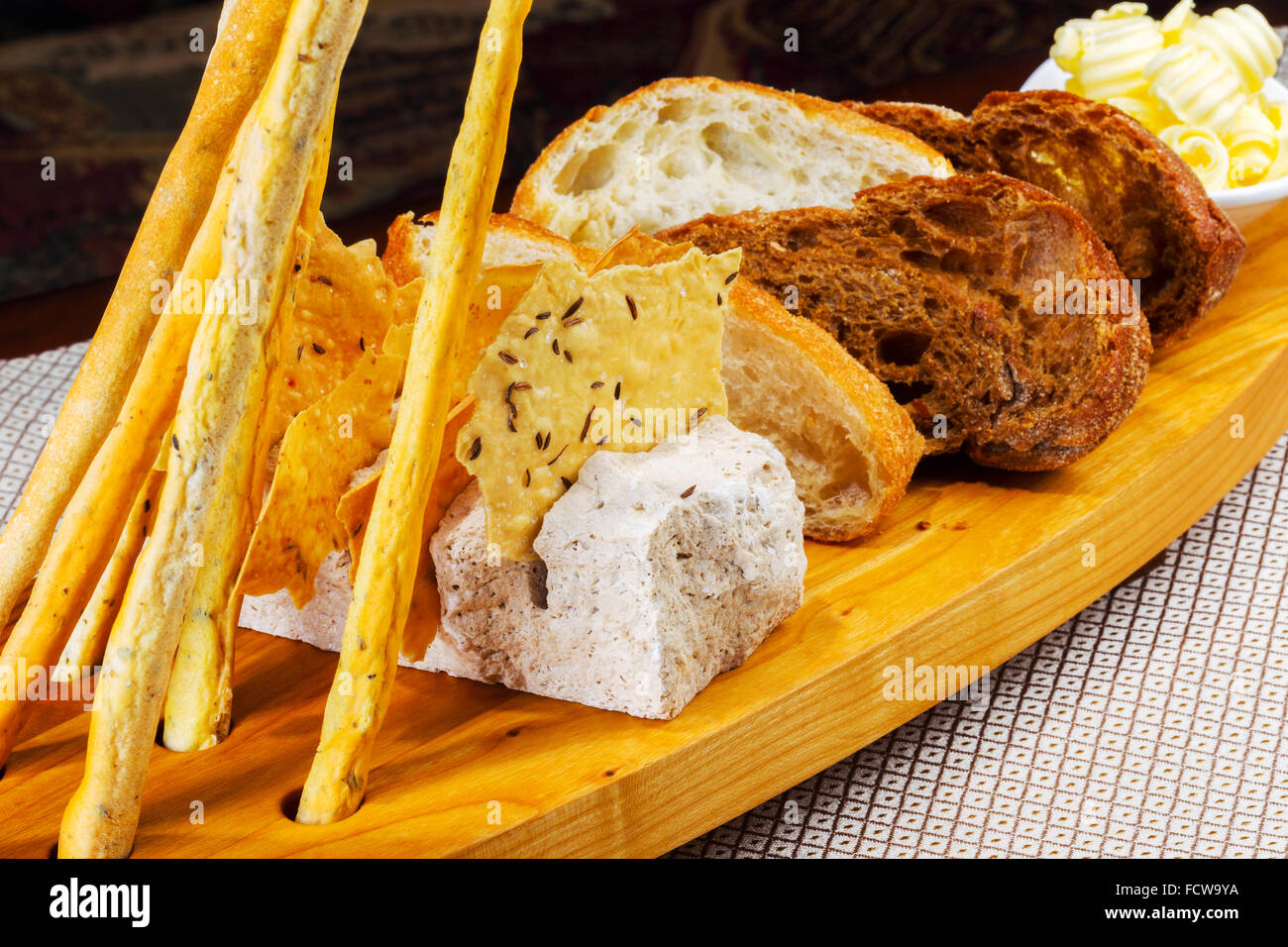 Various kinds of fresh baked bread loaves in wooden tray Stock Photo