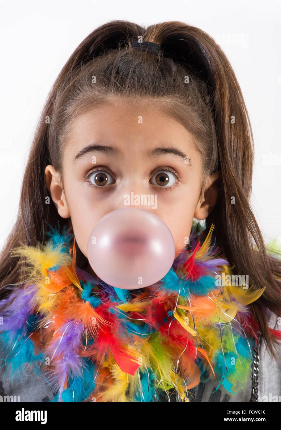 Cute little girl blowing a chewing gum bubble with wide surprised eyes and colorful feathers around her neck - Stock Image