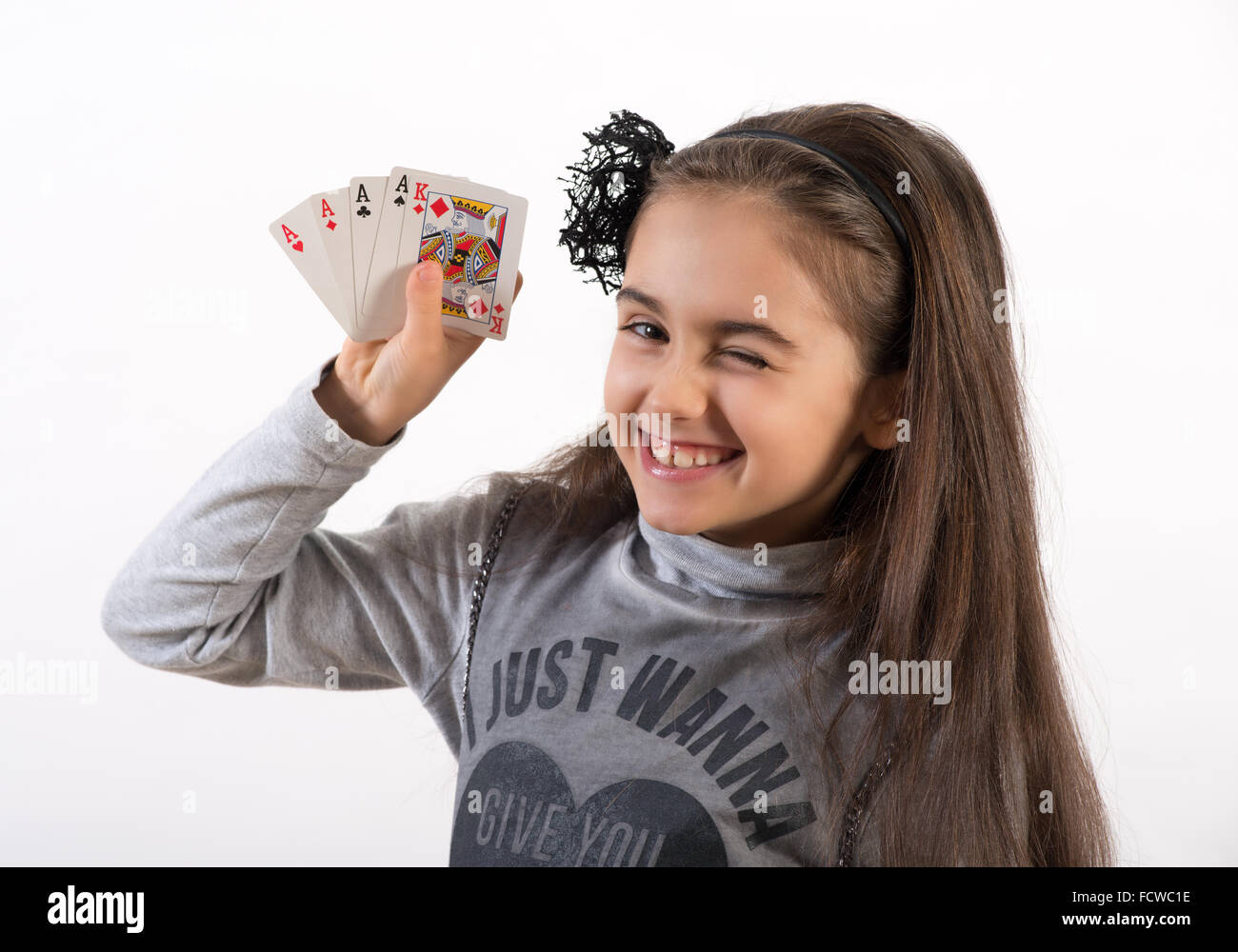 Lucky pretty little girl winking at the camera as she displays her poker hand of four aces and a king - Stock Image