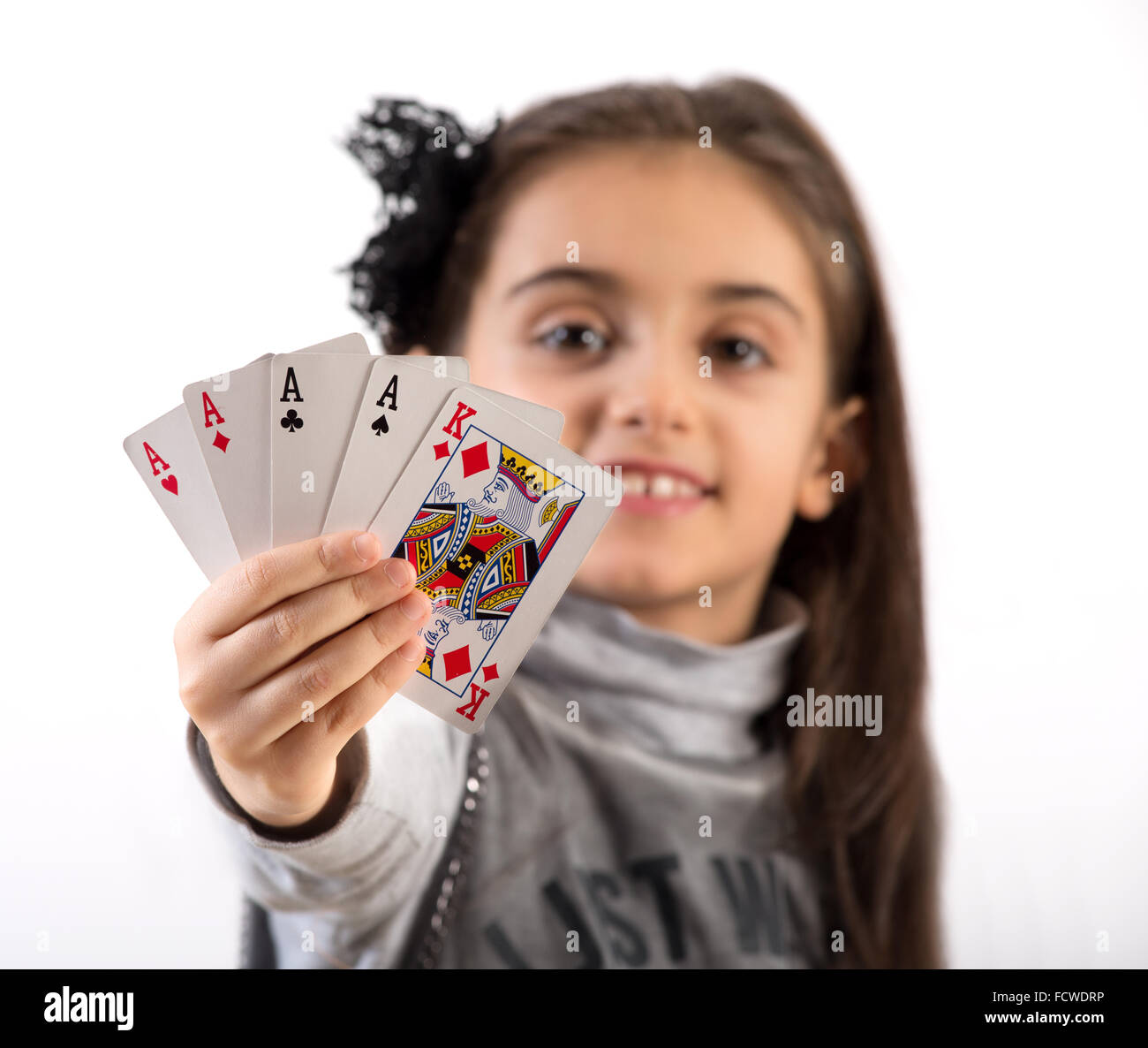 Proud little girl showing a winning poker hand of four aces and a king to the camera - Stock Image