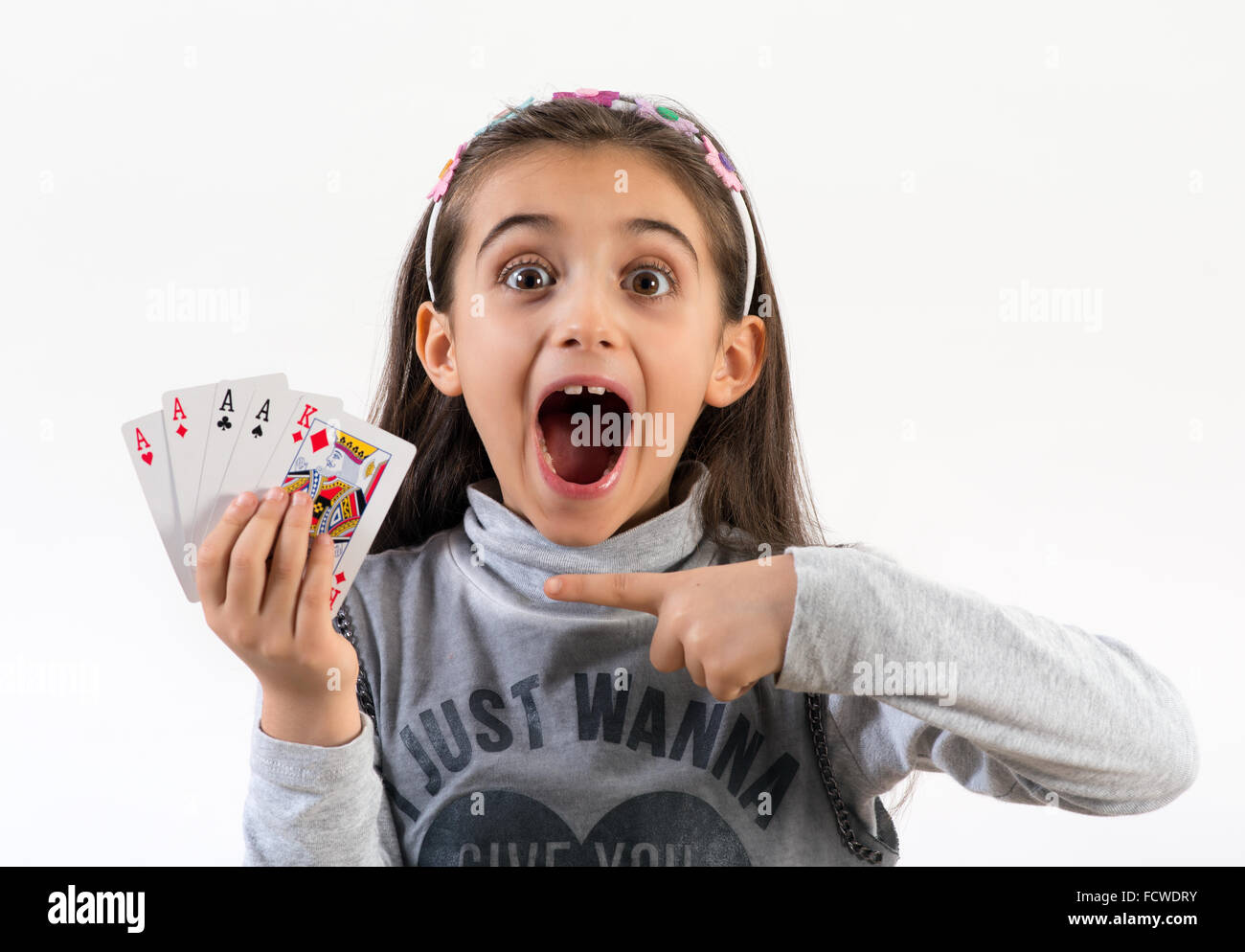 Excited little girl pointing to a winning poker hand - Stock Image